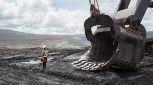 mining safety practitioner looks at bucket for hazards