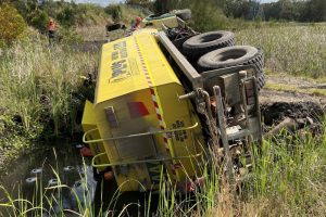 dangers of operating near water. truck on its side water storage dam